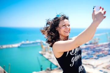 I love selfie! portrait of beautiful brunette girl taking photographs of herself, selfies, on the shore at seaside. modern concept of social life, instagram