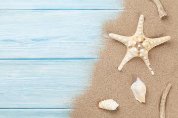 Sea sand with starfish and shells on wood