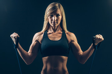 Athletic young woman working on biceps with expander