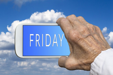 Smart phone in old hand with days of the week - Friday on screen