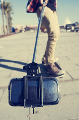 skater taking a self-portrait or a video with a selfie stick