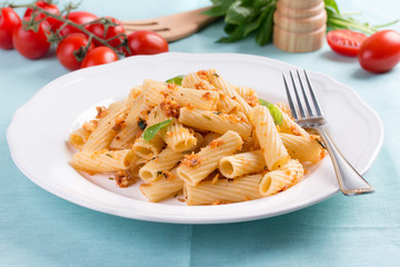 Plate of penne pasta with bread crumbs, basil and cherry