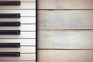 Inspirational background with a piano on a wooden table while composing. Top view and a copy space for editor's text.
