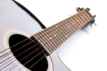 Black acoustic guitar on white background