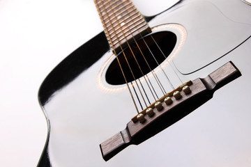 Black acoustic guitar on white background