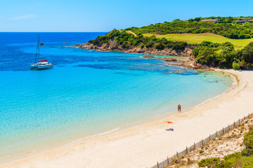 Unidentified couple of young people relaxing on beautiful Grande Sperone beach, Corsica island, France