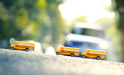 Yellow school buses toy model the road crossing.Shallow depth of field composition and afternoon scene.