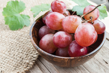 Red grape in wooden bowl on wooden table