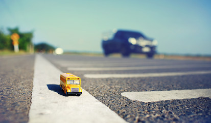 School bus toy model on country road background. Shallow depth o