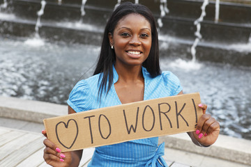 "A woman holding a sign saying ""love to work"" in front of a fountain."