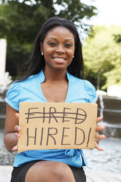 """A young woman smiles while holding a sign with the words """"FIRED"""" """"HIRED""""."""