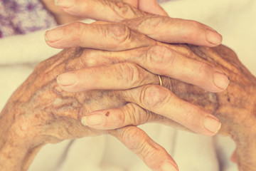 Hand of woman touching senior woman  in clinic. : Vintage filter
