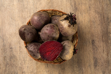 Some beets in a basket over a wooden surface