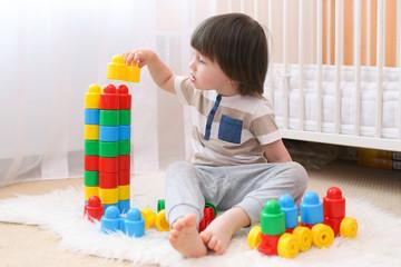 Cute little boy plays plastic blocks