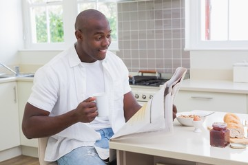 Smiling man reading a newspaper and drinking tea