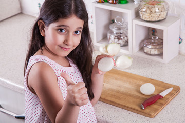 Beautiful little middle eastern 7 years old girl is working with knife and onion in the white kitchen. studio shot. with thumb.