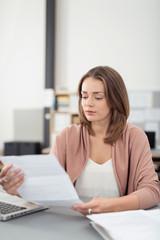 frau sitzt am schreibtisch im büro und liest einen brief