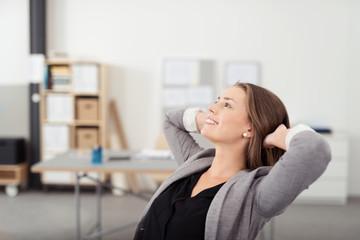 zufriedene geschäftsfrau im büro lehnt sich zurück