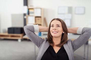 zufriedene geschäftsfrau im büro verschränkt arme hinter dem kopf