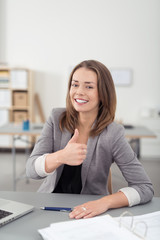 glückliche angestellte im büro zeigt daumen hoch
