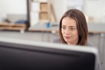 geschäftsfrau schaut konzentriert auf ihren computer
