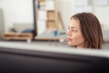 frau am computer schaut nachdenklich zur seite