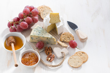 molded cheeses, fruit and snacks on a white wooden background