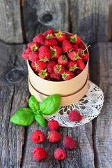 Raspberry in the round box with leaf of mint on the old wood background