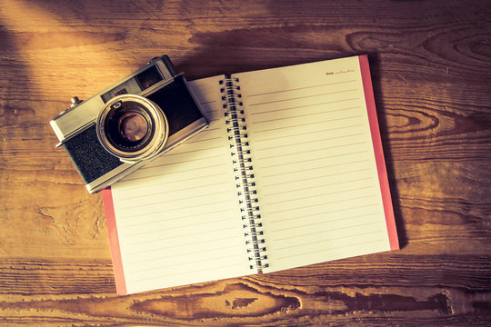 Blank notebook with fountain pen and retro camera on wooden tabl