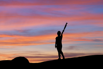 Silhouette of woman lifting tripod under the sky at sunset