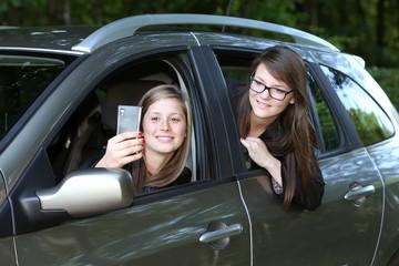 Deux jeunes filles se prenant en photo dans une voiture