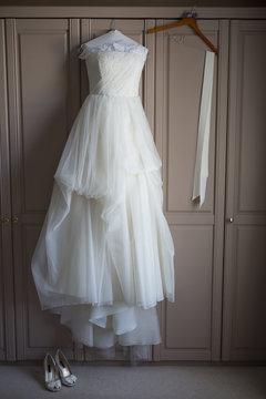 Wedding dress hanging on a wardrobe door, wedding shoes on the floor.