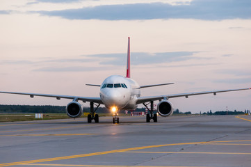 Perspective view of jet airliner at taxiway. Evening scene with