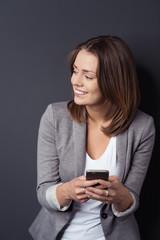 frau mit mobiltelefon schaut lächelnd zur seite