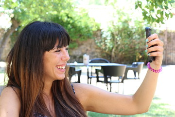 Young woman taking selfie outside