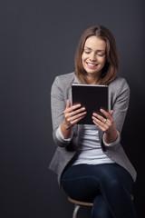 lächelnde frau liest nachrichten am tablet-pc