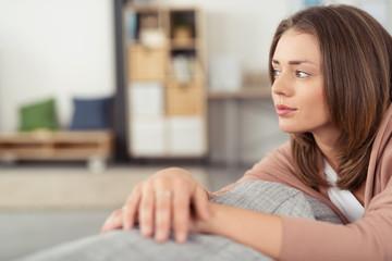 frau sitzt auf dem sofa und schaut in gedanken zur seite