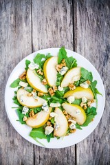 fresh salad with arugula, pear, walnuts and blue cheese