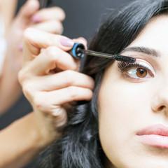 makeup artist doing make up for beautiful arabian woman