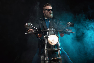 Macho businessman riding his motorbike in a suit