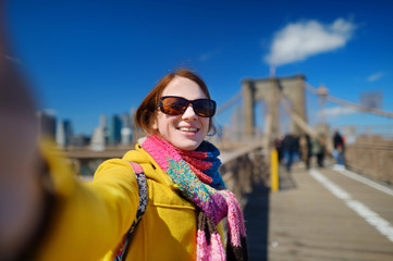 Young woman taking a selfie on Brooklyn Bridge