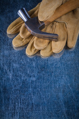 Pair of leather safety gloves with metal claw hammer on scratche