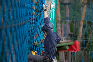 teenager climbing a rope park, boy climbing in adventure park