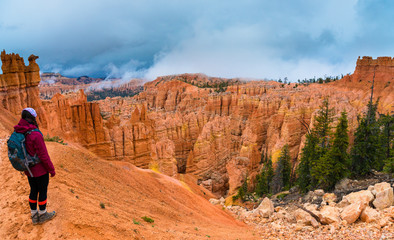 Hiker looking down a Peek-a-boo loop trail Bryce Canyon