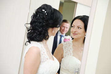 bride and groom standing in front of a mirror