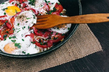 Cooking Fried eggs with tomatoes and onions in a pan
