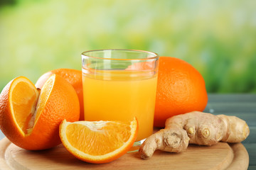 Fototapete - Glass of orange juice and slices on wooden table, on bright background