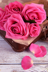 Beautiful pink roses in suitcase, closeup