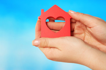 Female hands with model of house on color background
