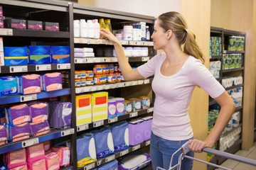 Pretty woman picking product in shelf